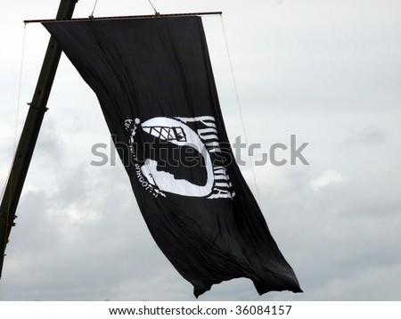 POW MIA Flag flying high from a crane against an overcast sky. Zdjęcia stock ©
