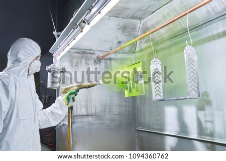 Powder coating of metal parts. Worker wearing protective wear performing powder coating of metal details in a special industrial camera. Hand holding powder coating sprayer #1094360762