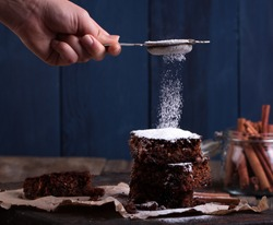 Powder of sugar is hung on a Pieces of Christmas chocolate cake on wooden background.