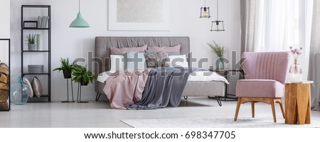 Powder pink chair standing in a bedroom next to a wooden stool and a flower on it