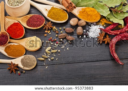 Powder spices assortment on spoons in black wooden table background