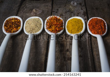 Powder spices on spoons in vintage wooden table background #254163241