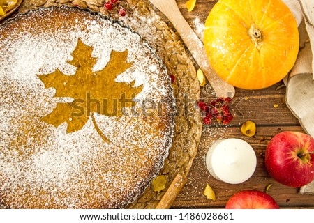 Powdered maple leaf on homemade cake. Autumn concept, autumn background, homemade cake with decoration in the form of an autumn leaf. Homemade cake with icing sugar on the table. Save the space
