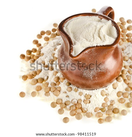 powdered milk drink in a clay jug  with soy beans on white background