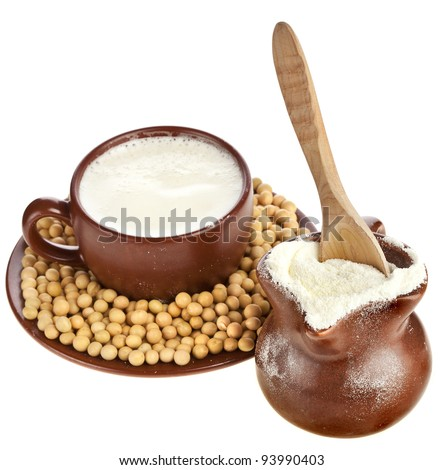 powdered milk drink in clay pitcher , soy beans  and a clay cup on white background