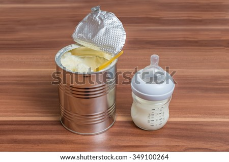 Powdered milk formula in can and bottle for feeding baby on wooden table.