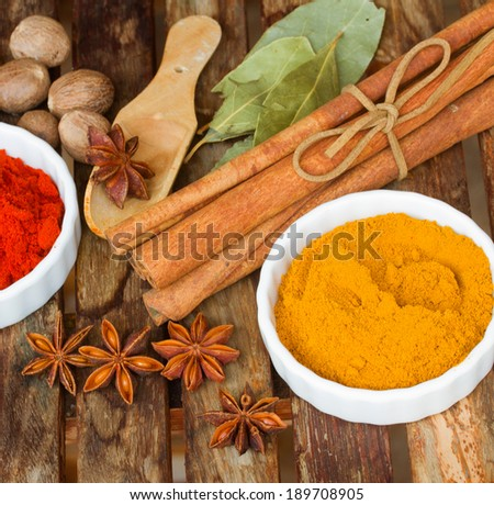powdered  spices of curry and red pepper with seeds of anise and cinnamon on wooden table