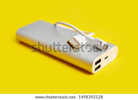Power bank for charging mobile devices. White smart phone charger with power bank. Battery bank on a yellow background . External battery for mobile devices. #1498392128