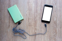 Power bank, Smart phone and USB cable on wooden background