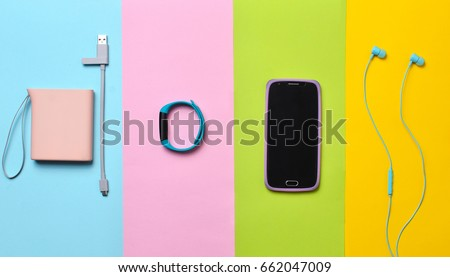 Power bank, smart watches, headphones, smartphone lined on a colorful background. Top View