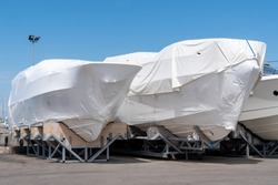 power boat parked covered white protective plastic film New boats in cover casing shrink wrap on sailboat stored for winter