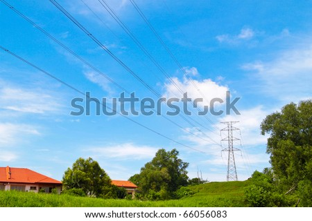 Power cable tower on a hill near housing area. Concept of power transmission.