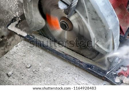 Power Circular Saw Blade Cutting Fresh Concrete