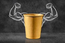 Power coffee. Cup of coffee on the background of depicted muscles on chalkboard. Strong power, muscle arms. Power concept.