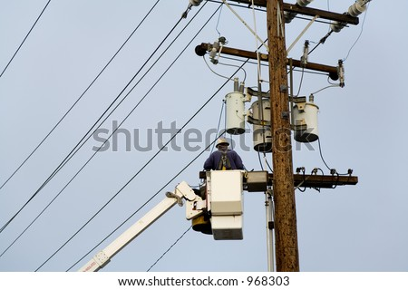 Power company worker wearing a hardhat is repairing electrical wires from a utility bucket truck.