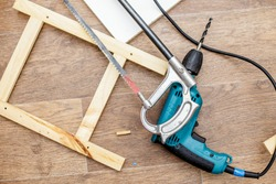 Power drill, hacksaw and wood products lay on a floor ready to work