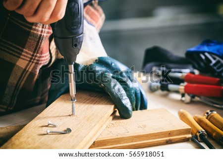 Power electric screwdriver. Carpenter working with a hand tool on the work bench. Closeup view