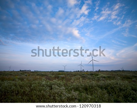 Power generating wind mill farm with cloudy sky in the background.