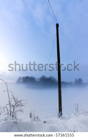 Power line or telephone line to a remote house in a foggy winter evening