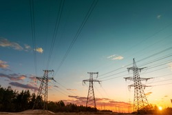 power line pylons during sunset with beautiful saturated sky. distribution, transmission and consumption of electricity