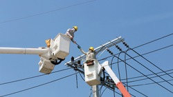 Power line support, insulators and wires. Appearance of a design. Assembly and installation of new support and wires of a power line. electricians repairing wire on electric power pole.