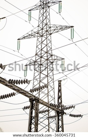 power line tower,high voltage isolators,wires,against light sky