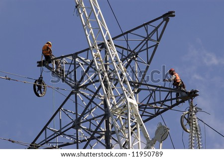 stock photo : Power linemen at work up on a pylon tower.