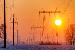 Power lines in the cold winter morning. Energy and electricity distribution in winter.