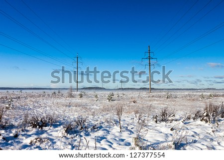 Power lines in winter snow field on a background of the blue sky
