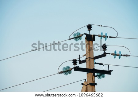 Power lines on background of blue sky close-up. Electric hub on pole. Electricity equipment with copy space. Wires of high voltage in sky.