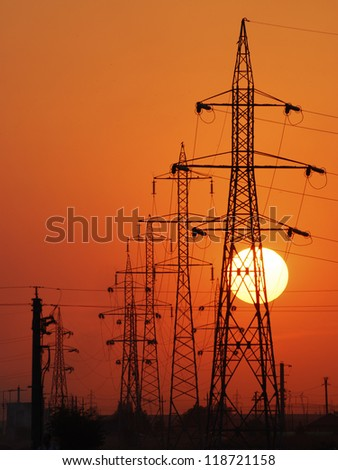 Power lines poles over setting sun