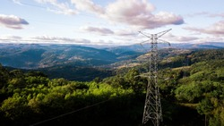 Power Lines with beautiful forest background against sky and mountains