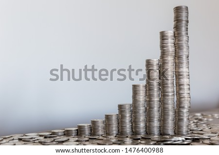 Power of compound interest on your savings illustrated with coins stacks.