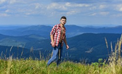Power of nature. Man unbuttoned shirt stand top mountain landscape background. Strong hiker muscular torso. Athlete muscular guy relax mountains. Hiking concept. Muscular tourist walk mountain hill