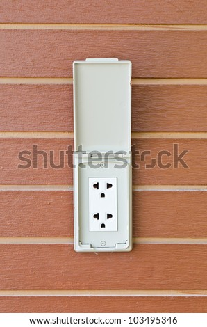 power outlet on wooden wall.