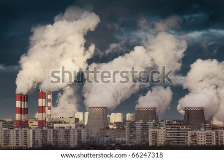 Power plant smokestacks emitting smoke over urban cityscape