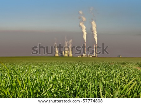 power plant with smoking chimney on green grass