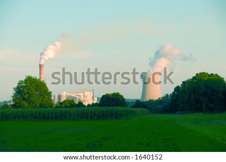 Power plant with steam coming from the stacks, in the country behind a farmer's field.