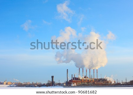 Power plant with white smoke over blue sky