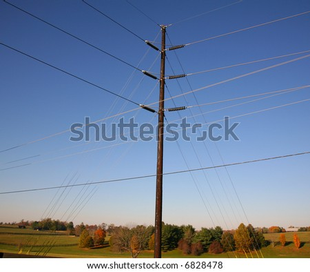 Power Pole Maze of Wires in front of Autumn Pasture Scene