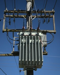 Power pole mounted mains High voltage three phase transformer against a clear blue skye and showing some of the transmission lines and fixing hardware