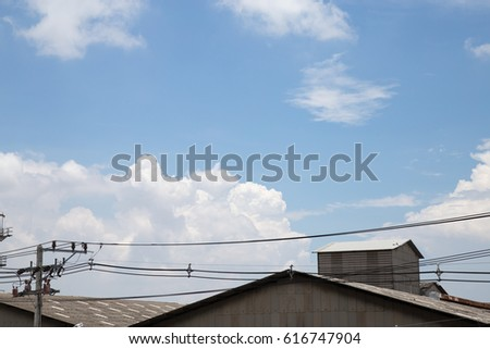 Power poles and wires with industrial roofs on a white cloud and clear blue background #616747904
