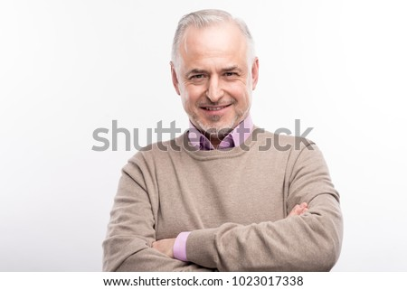 Power pose. Pleasant grey-haired bristled man folding his hands across his chest and smiling at the camera while posing isolated on a white background #1023017338