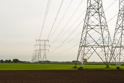 Power pylons and high power lines in a green field on a cloudy in the fall season.