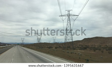 Power pylons and high voltage electric cables crossing freeway and disappearing into mountains, Apple Valley region, California. Overcast day #1395631667