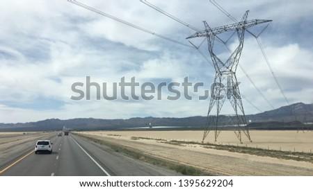 Power pylons bearing high tension electricity cables crossing Interstate 15 near massive solar power generators. Mojave Desert, California. #1395629204