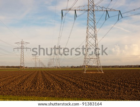 Power pylons in a rural countryside in the Netherlands. It is winter.
