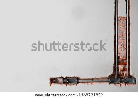 power receptacle steel boxes and conduit have install in the old brick wall #1368721832