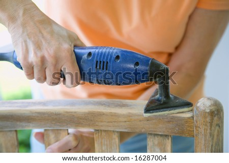 Power sanding an old wooden chair.