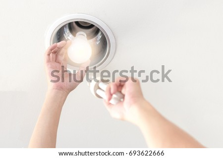 Power saving electrical efficiency concept. Hands changing compact-fluorescent (CFL) bulbs with new LED light bulb.